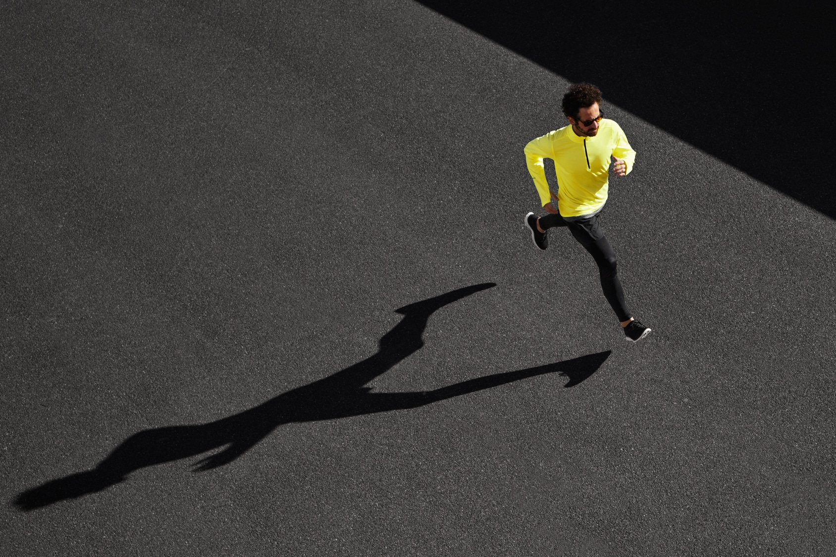 Running man sprinting for success on run. Top view athlete runne