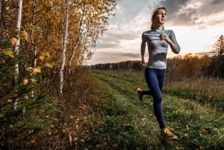 Woman running in autumn forest