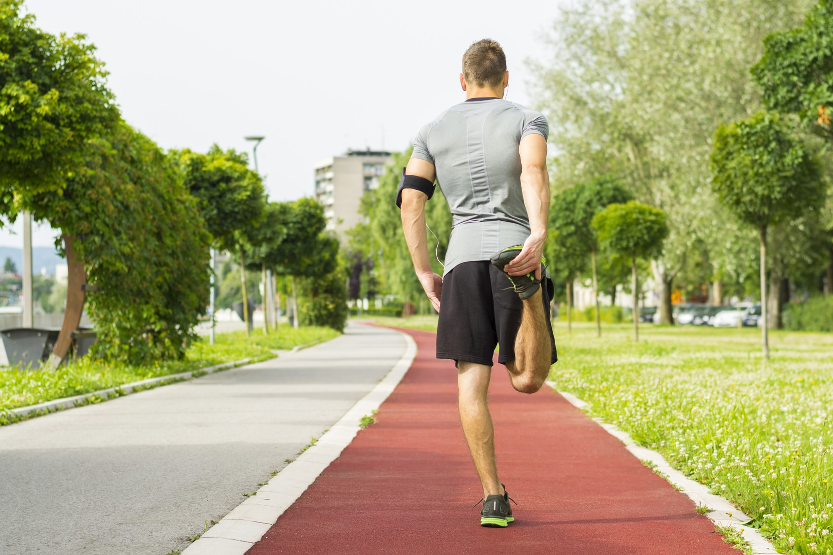 young fitness man runner stretching legs before run